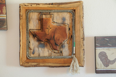 Mesquite framed Texas This State of Texas is cut from a single piece of mesquite with natural cracks filled with black wood inlay.  A Cross has been etched in the piece and filled with turquoise inlay.  Mounted on oak with barbed wire outline.  This piece is mounted in a natural edge mesquite frame with lariat lining.