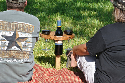 """Park picnic wine table: It folds up and has a built in handle for carrying.  Insert the pointed peg into the ground. Fold the table top over on its wooden hinge. Then, enjoy a nice bottle of wine without concern of where to set your wine bottle or tipping over your glasses. This solid oak table is 12"""" in diameter and has more than enough room for light snacks!"""