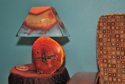 Hand carved, mesquite log, lamp with turquoise inlay.  Fitted with a copper lampshade with horse decor outline