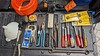 """Tools from San Mateo and San Bruno, Top Left 3/8"""" air hose like new, Flotec pump, 3x Irwin Forstner bits, mixed set of socket drivers, including Craftsman and XCelite, Bonaloy 15/16 - 1"""" wrench, unmarked ChannelLcok pliers, Crestaloy needle nose, Stearns file holder missing the screw, ChannelLock 350A pliers, putty knife, Made in USA Vise Grip clamp, missing the swivel pads,  Lenox hole saw arbor, hose end device, shop funnel, and 16' Starrett tap, box of single edge razor blades."""