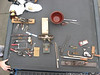 """Top Left - Kirk's B Plane 15"""" Transitional, calipers and dividers, and a Hyde knife<br /> Below: Kasper' Shaves, ratchet driver, RJ bit Box, gizmo drill, clamps knives<br /> Center, MS KK compass plane, 2-hole punch, tongs, Teeny tiny spoke pointer, tiny hacksaw<br /> Lower Right Tom's yankee, small hacksaw, mat cutter, Lufkin micrometer, dividers compass, trammel point and drafting pen<br /> Lower Right also : Joe Parker's india slip stone<br /> Top Right Scott's  leather tool, aligment / pry bars, depth micrometer, blackhawk flex head ratchet"""