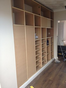large storage cupboard with lots of sections , skirting runs around it