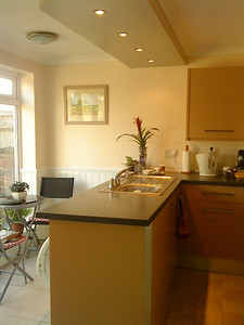 Howden Kitchen.Island with sink. washing machine in back for easy access in breakfast area. Silver Formica plinth with matching light pelmet feature.
