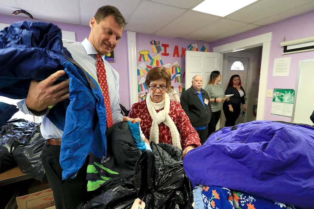 . Worcester County Sheriff Lewis G. Evangelidis distributed thousands of winter coats to families & charitable organizations in need throughout Worcester County for the Sheriff�s Annual Winter Coat Drive on Wednesday, December 5, 2018. One of their stops was the Spanish American Center in Leominster which got about 600 of the jackets they collected. Evangelidis helps Sonia Rodriguez, staff member at the center, organize the jackets before they gave them out. SENTINEL & ENTERPRISE/JOHN LOVE