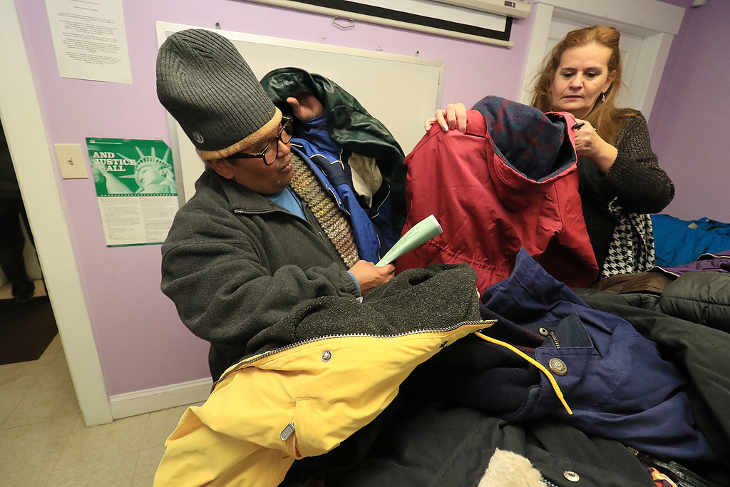 . Worcester County Sheriff Lewis G. Evangelidis distributed thousands of winter coats to families & charitable organizations in need throughout Worcester County for the Sheriff�s Annual Winter Coat Drive on Wednesday, December 5, 2018. One of their stops was the Spanish American Center in Leominster which got about 600 of the jackets they collected. Albarto Toro sifts through the pile of jackets looking to get one for each member of his family with help from Silvia Taurino a Center Board Member. SENTINEL & ENTERPRISE/JOHN LOVE