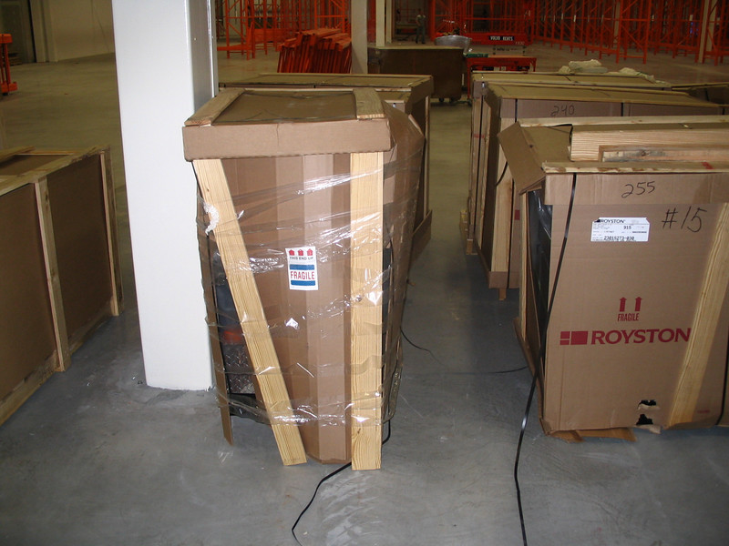 Note missing skid, damaged and missing straps, damaged wood supports, crushed cardboard, and clear wrapping tape added to package