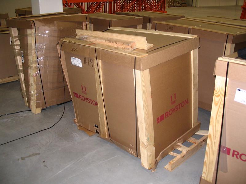 Note damaged wood skid, broken packing strap, and damaged cardboard
