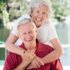 A married couple in their eighties show affection on their outdoor deck.