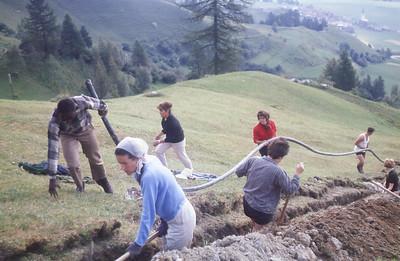 Glover Lee pulls the pipe up hill.  Gunhild Pedersen in scarf, Ella Schanz in black top, Christel Schulz in black shorts in ditch, Barbara Stein in red, Rainer Charbonnier in white top, Vreni  Wiesendanger in ditch in black top.