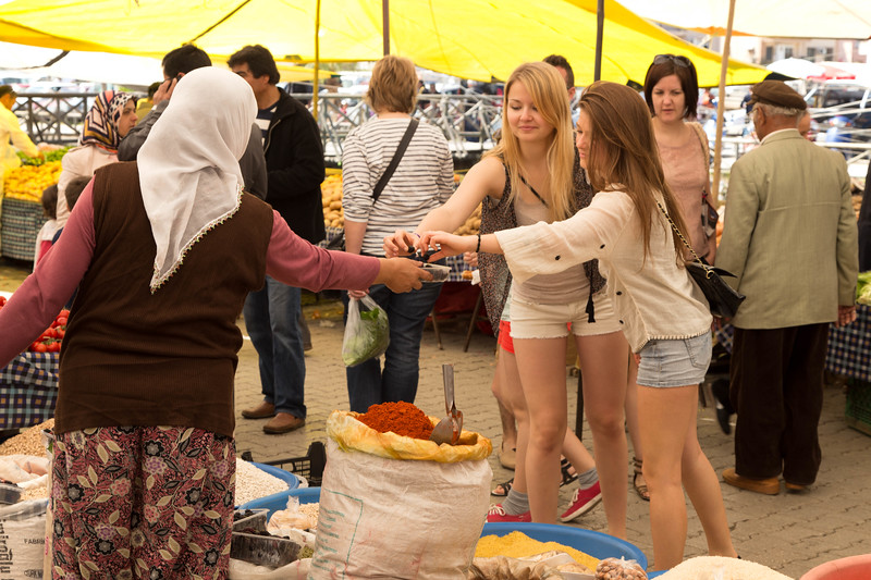 Young Europeans sample some olives from a seller at the Fethiye market.