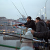 Men fishing off a busy bridge in Istanbul.  They catch very small fish.