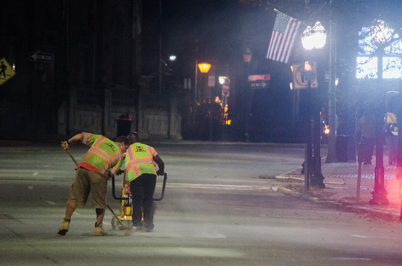Fitchburg DPW workers grind down the paint on Main Street to begin the process of converting it to one lane on Tuesday evening. SENTINEL & ENTERPRISE / Ashley Green