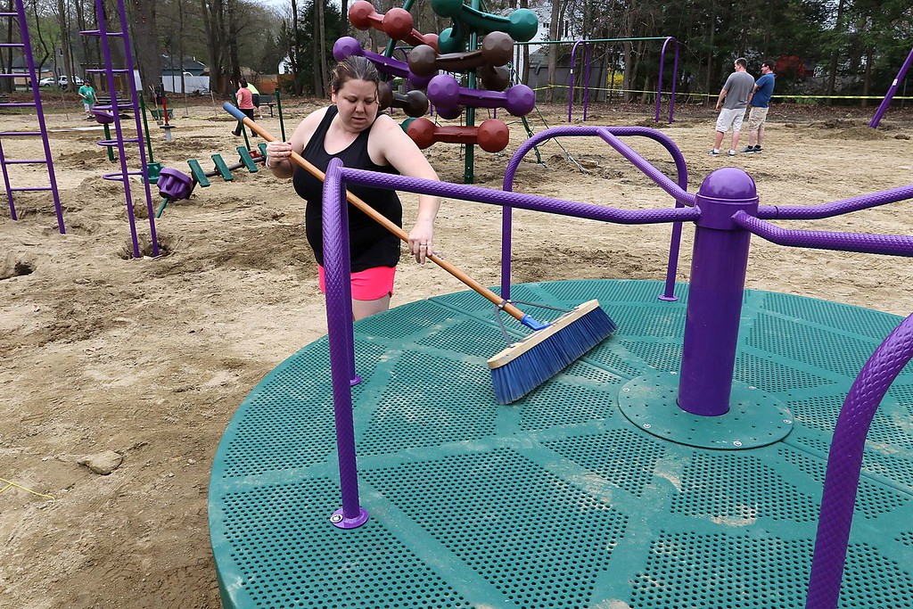 . Work was underway to put in Wallis Park Playground that was funded through a citizens petition on Friday morning in Lunenburg. Ashley Shaw, who lives across the street from the park, cleans off the Merry Go Round that had just been put in. SENTINEL & ENTERPRISE/JOHN LOVE