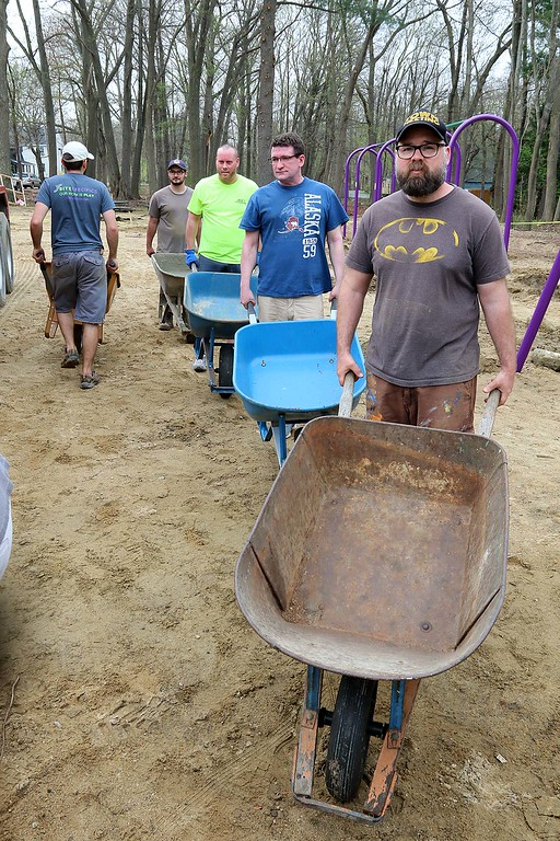 . Work was underway to put in Wallis Park Playground that was funded through a citizens petition on Friday morning in Lunenburg. Many lined up with wheelbarrows to get some cement to secure all of the playground equipment in the ground. Up front leading the way is Lunenburg resident Christopher Letarte who lives near the park with his family. SENTINEL & ENTERPRISE/JOHN LOVE