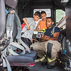 Springfield Firefighter Lamond Lawrence shows a thermal imaging device to Omar Rojas, 8, left, and Joshua Rosemond, 9, both of Springfield, at Springfield BID's Cruise Night at Court Square on Monday. (Steven E. Nanton photo)