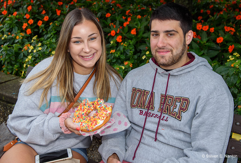 Danielle Yostpille, of Long Island, New York, has a Jumbo Doughnut with Fruity Pebbles with Frank Dean, of Westchester, New York, on the second day of The Big E 2019 on Saturday in West Springfield. (Steven E. Nanton photo)