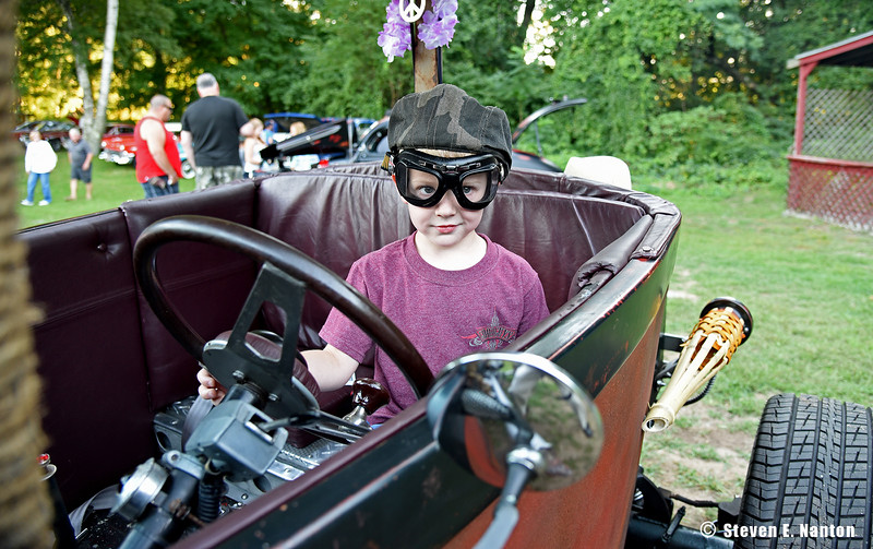 Wearing old-style goggles, Reid Flanagan, 4, of Westfield, tries out a rat rod for size at Ludlow Elks Lodge 2448's weekly Cruise Night on Tuesday. (Steven E. Nanton photo)