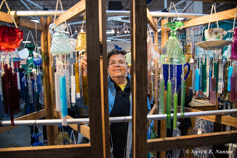 Ann Torrex of The Crafty Peddler arranges some wind chimes at the Old Deerfield Spring Sampler Craft Fair at the Big E in West Springfield on Saturday. (Steven E. Nanton photo)