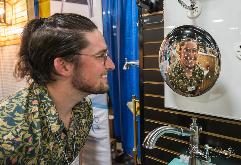 Sean O'Rourke of Frank Webb Home is reflected in a shower head at the 66th Annual Western Mass. Home & Garden Show at Eastern States Exposition on Friday. (Steven E. Nanton photo)