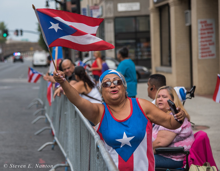 Aida Flores, of Springfield, waves the Puerto Rican flag at the Springfield Puerto Rican Parade on Main Street on Sunday. (Steven E. Nanton photo)