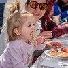 Juliana Dixon, 1 1/2, of Southwick, takes a big bite of her pancake as her mother, Stacey Dixon, looks on at the 2019 World's Largest Pancake Breakfast in downtown Springfield on Saturday. (Steven E. Nanton photo)