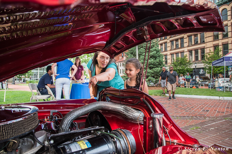 Rebecca Aguilar explains parts of an engine of a 1953 Buick Roadmaster to her daughter, Dianira Severino, 6, both of Springfield, at Springfield BID's Cruise Night at Court Square on Monday. The car is owned by Dan Czochara, of Ludlow. (Steven E. Nanton photo)