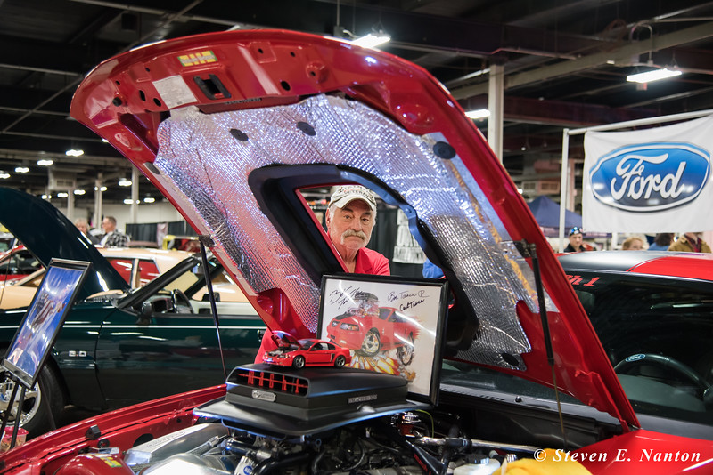Jack Gahr, of Hartford, is seen through the hood opening of his 2004 Ford Mustang Mach I at Frank Maratta's Auto & Race-A-Rama show at  Eastern States Expositionin West Springfield on Friday. (Steven E. Nanton photo)