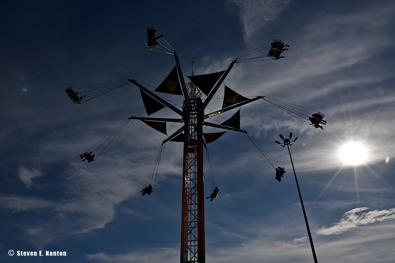 Riders are silhouetted in the sun on a giant pinwheel ride on Springfield Day at The Big E in West Springfield on Monday. (Steven E. Nanton photo)