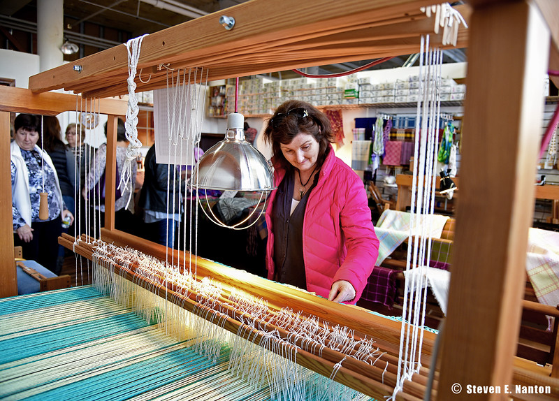 Ellen Richard, of Hampden, looks over a fabric loom in the Cat's Cradle Design studio at the Fall Open Studios Art Show & Sale at Indian Orchard Mills in Springfield on Saturday. The show continues on Sunday. (Steven E. Nanton photo)