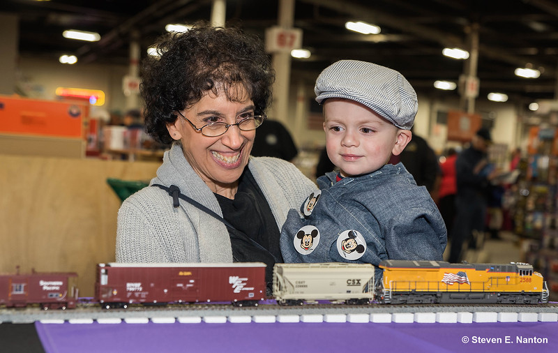 Sharon Benoit, of East Longmeadow, holds her grandson, Ryan Giguere, 2, as they look over trains at the 50th Anniversary Railroad Hobby show at Eastern States Exposition on Saturday. (Steven E. Nanton photo)