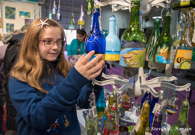 Madyson Millier, 10, of Plainville, Connecticut, looks over some decorated bottles at Sand and Water Creations in Glass at the Old Deerfield Spring Sampler Craft Fair at the Big E in West Springfield on Saturday. (Steven E. Nanton photo)