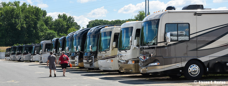 A couple walks past a row of motor homes at the Family Motor Coach Association's 94th Family Reunion and Motorhome Showcase on Wednesday at The Big E in West Springfield. (Steven E. Nanton photo)