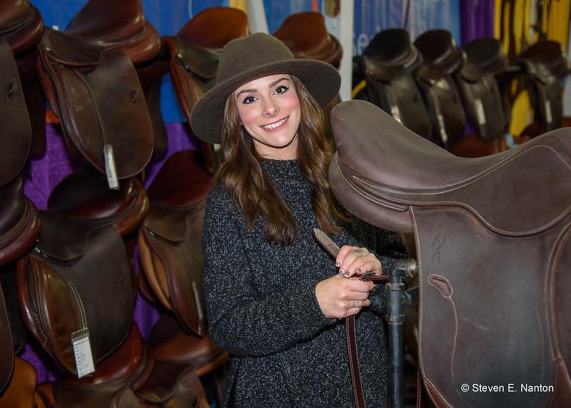 Ricki Corrieri of Equitack adjusts a saddle on display at Equine Affaire on Friday. (Steven E. Nanton photo)