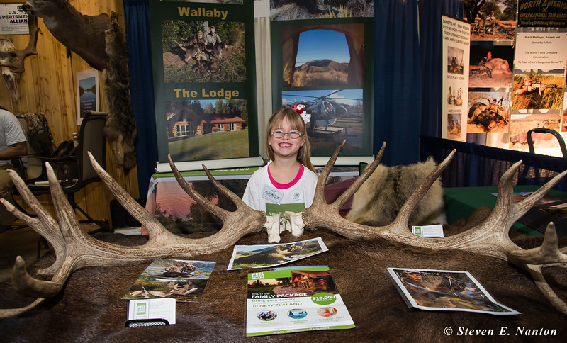 Ava White, 5, stands behind a pair of giant antlers at the Peel Forest Safaris booth at the 2017 Springfield Sportsmen's Show at the Big E in West Springfield on Friday. (Steven E. Nanton photo)