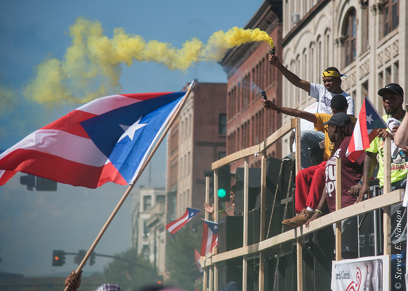 Youths on a float release colored smoke at the Springfield Puerto Rican Parade on Main Street on Sunday. (Steven E. Nanton photo)