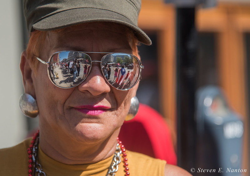 the parade scene is reflected in the sunglasses of Carmen Burgoan, of Springfield, at the Springfield Puerto Rican Parade on Main Street on Sunday. (Steven E. Nanton photo)