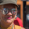 the parade scene is reflected in the sunglasses of Carmen Burgoan, of Springfield, at the Springfield Puerto Rican Parade on Main Street on Sunday. (Steven E. Nanton photo)