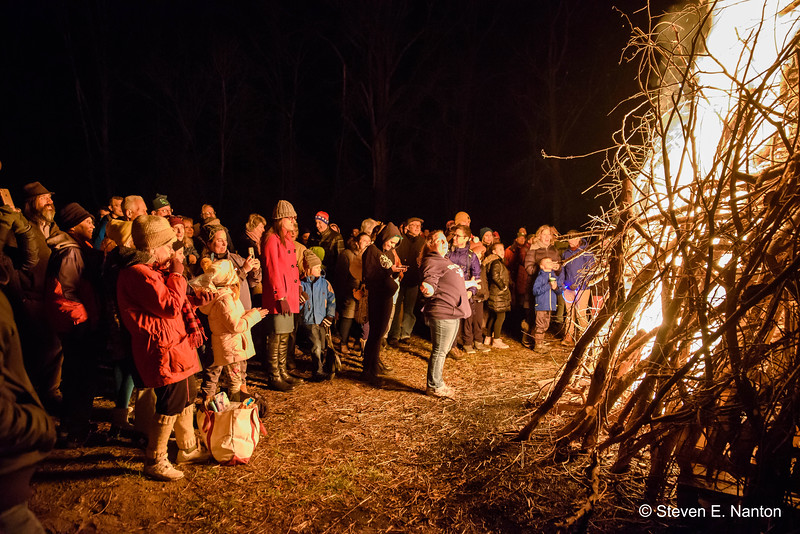 People bask in the warmth of the bonfire during the celebration of winter solstice at  Arcadia Wildlife Sanctuary in Easthampton on Friday night. (Steven E. Nanton photo)