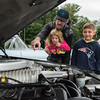 Jason Lage shows a car engine to his children, Lily, 3, and Jaden, all of Ludlow, at Ludlow Elks Lodge's Cruise Night on Tuesday at 69 Chapin St. (Steven E. Nanton photo)