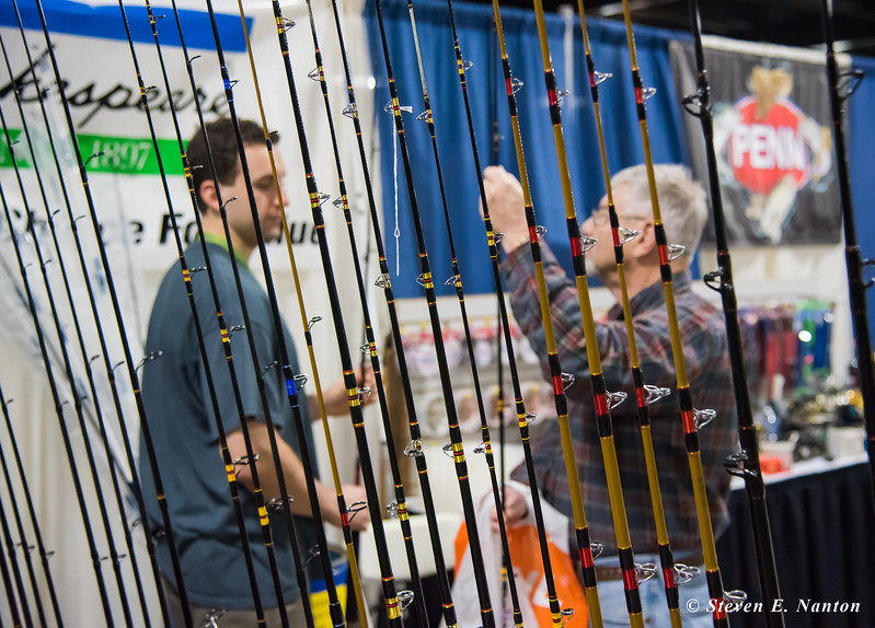 John Sansonetti, left, of Reel Deal, shows fishing rods to Skip Mastroianni, of Westfield, at the 2017 Springfield Sportsmen's Show at the Big E in West Springfield on Friday. (Steven E. Nanton photo)