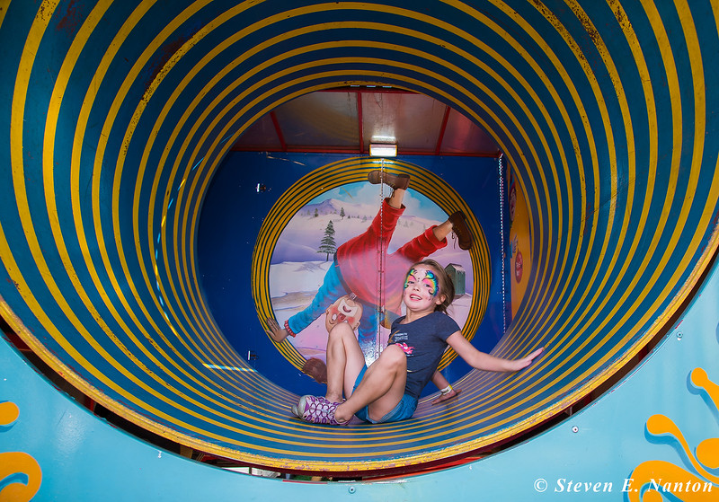 Madison Phelps, 6, of Springfield, takes a tumble in the Fun House's roating barrel on Salute to Chicopee Day at the Big E on Tuesday. (Steven E. Nanton photo)