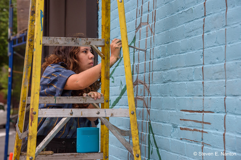 Salome Cortes, of Colectivo Morivivi of Puerto Rico, works on a mural on Hampden Street during Fresh Paint Springfield, a mural festival,  on Sunday. (Steven E. Nanton photo)