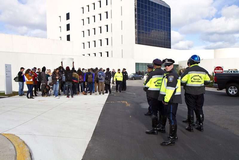 Occupy UMass Boston protestors facing off with 3 different police forces at JFK Library at Occupy UMass Boston March and Rally. November 11, 2011. Creative Commons BY-NC-SA 2011 Jason Pramas.