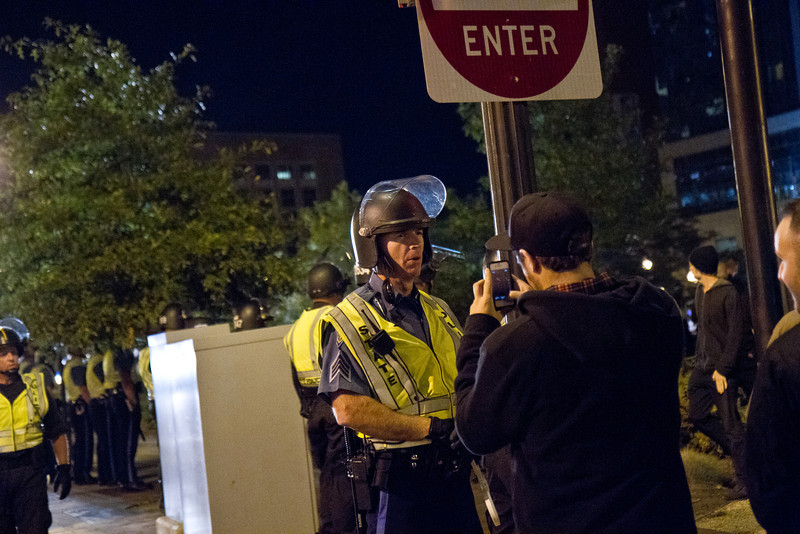 Protestor takes photo of State Police trooper during the destruction of Occupy Boston Camp 2, Oct. 10, 2011. Creative Commons BY-NC-SA 2011 Jason Pramas.