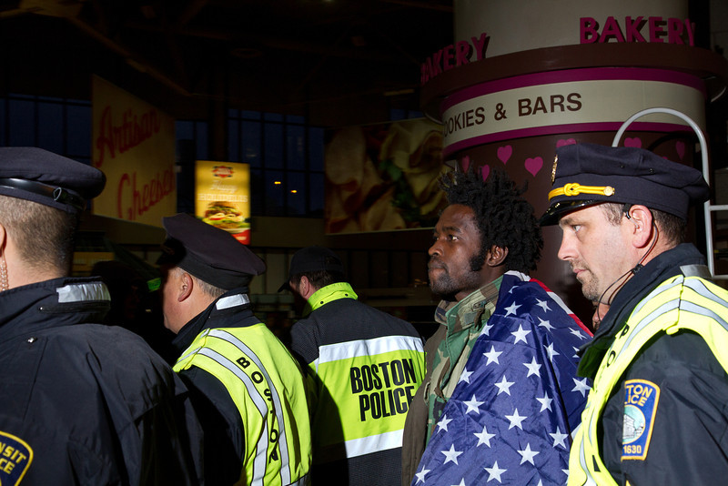 A dozen police escort a deaf Occupy Boston protestor after his arrest in the South Station men's room, Dec. 9, 2011. Creative Commons BY-NC-SA 2011.