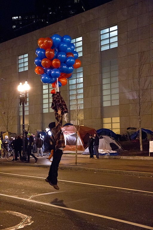 Protestor hangs from balloons on Atlantic Ave. during the defense of the Occupy Boston main encampment, Dec. 8, 2011. Creative Commons BY-NC-SA 2011 Jason Pramas.