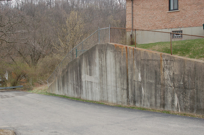 Concrete wall on the north side of the first building on the left.