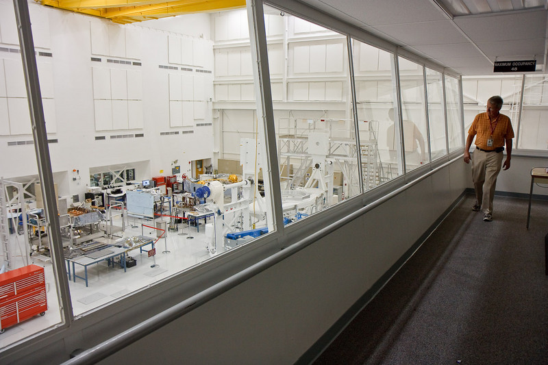 The viewing gallery in the Spacecraft Assembly Facility (SAF for short). <br /> <br /> SAF is a giant clean room, clean enough to perform surgery in.<br /> <br /> In the far corner of the room is the MSL cruise stage. To the left of it is the rover chassis.<br /> <br /> All these photos were taken through these one inch thick plexiglass windows. Given the reflections, nose and hand prints, I'm very pleasantly surprised these photos came out as clear as they are.