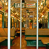 """This photo and the next 4 are of a subway car circa 1930's. My boss took one look at this car and said """"This thing is a death trap!"""" Notice the open circular fans in the ceiling and the bare incandescent bulbs. The seats look comfortable tho. And the advertisements were fun."""