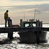 <div align=left>Calvin Jackson waiting at his boat for additional help unloading supplies. <em>Photo credit: Peggy Wilkinson</em></div>